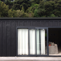 Waiheke Bach exterior - black stained board and batten